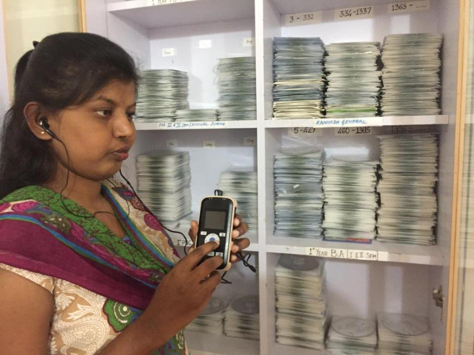 Mitra Jyothi beneficiary listening to Audio Books on a DAISY Player. Seen behind her is the Library's Master CD collection